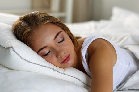 49108181 - young beautiful lonely blonde woman portrait lying in bed sleeping at home late in the morning after hard working day tired. sweet dreams, good morning, new day, weekend, day off, holidays concept